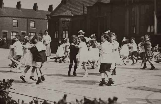 gray scale photo of children dancing on street